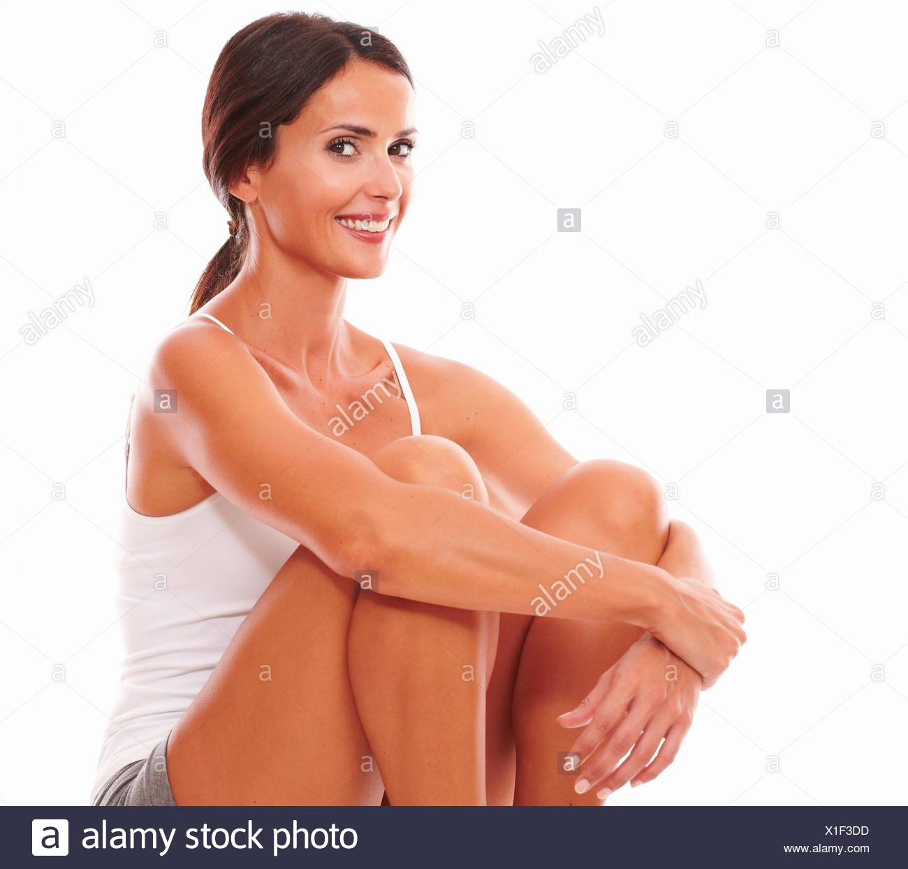 Lovely sporty woman baring fair skin while looking at you on isolated background. - Stock Image