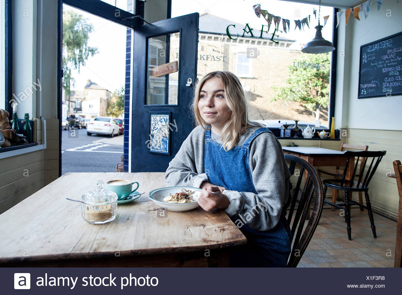 Young woman in cafe, eating muesli - Stock Image