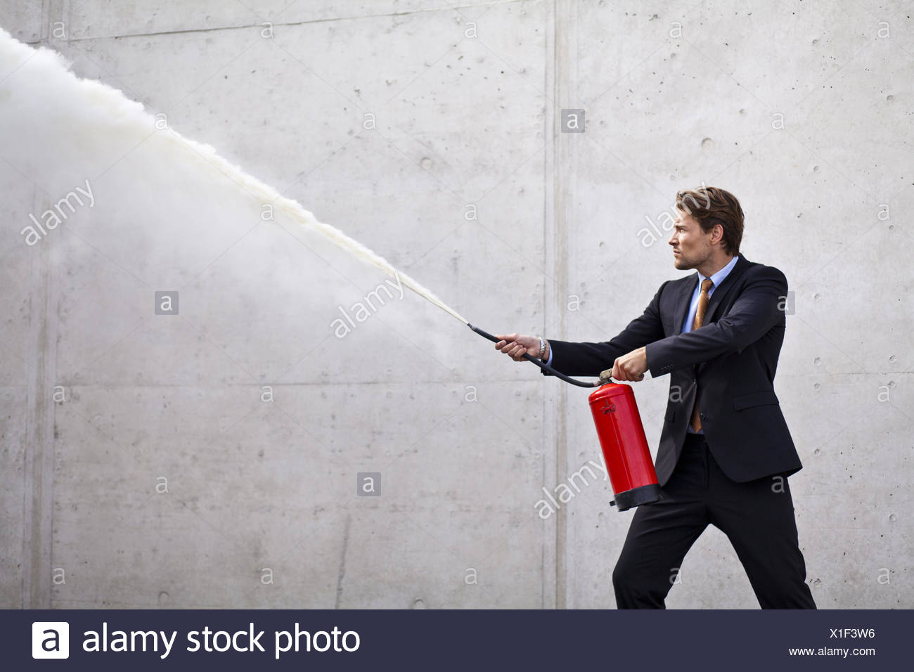 Focused businessman using a fire extinguisher - Stock Image