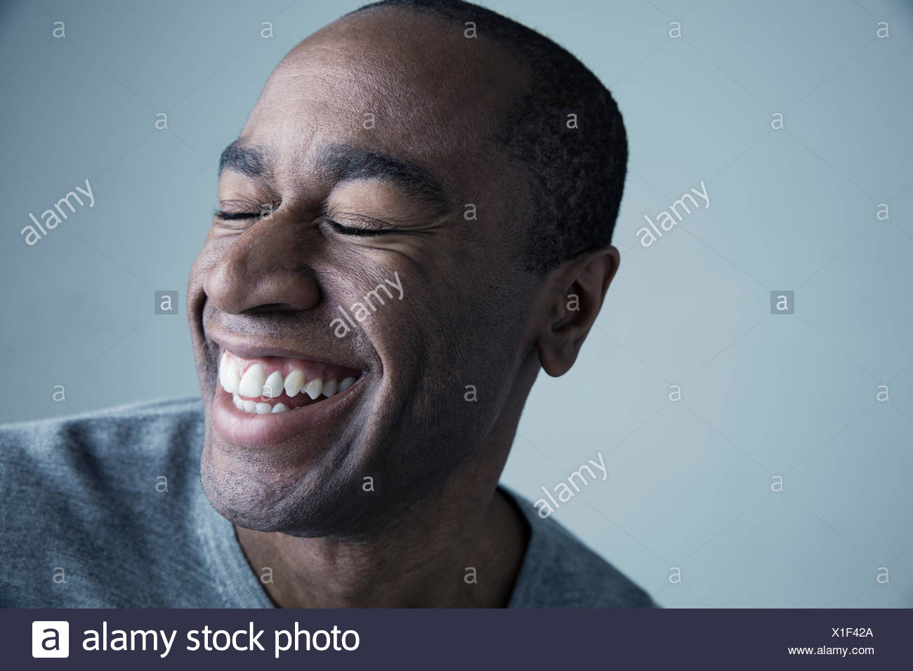 Portrait African American man smiling with eyes closed - Stock Image