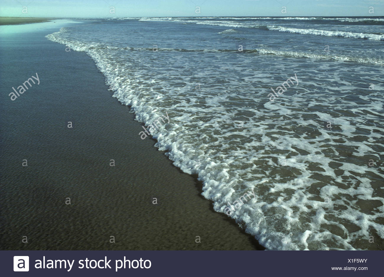 Gentle breaking waves on a sandy beach in the UK - Stock Image