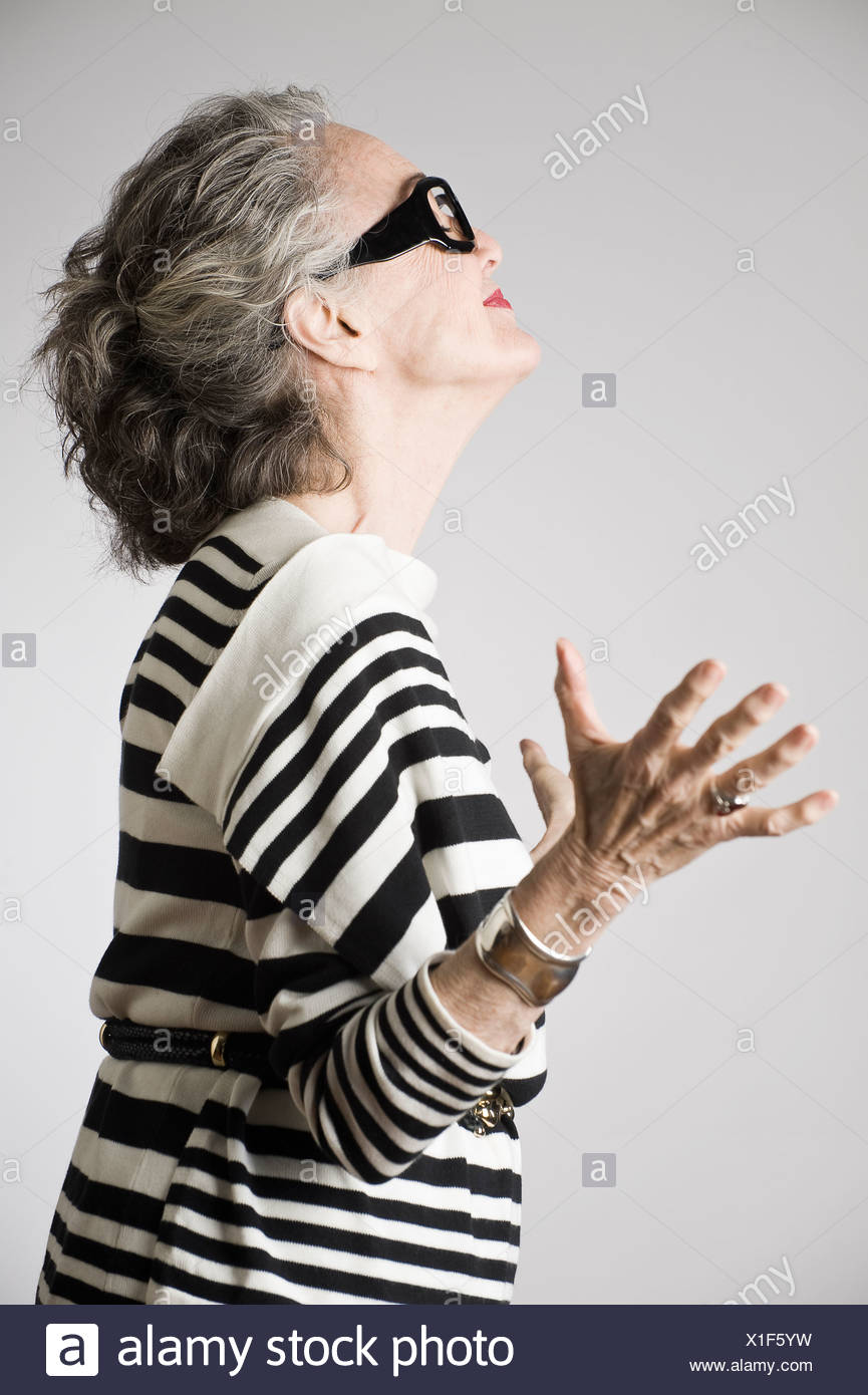Portrait of senior woman, arms open, side view - Stock Image