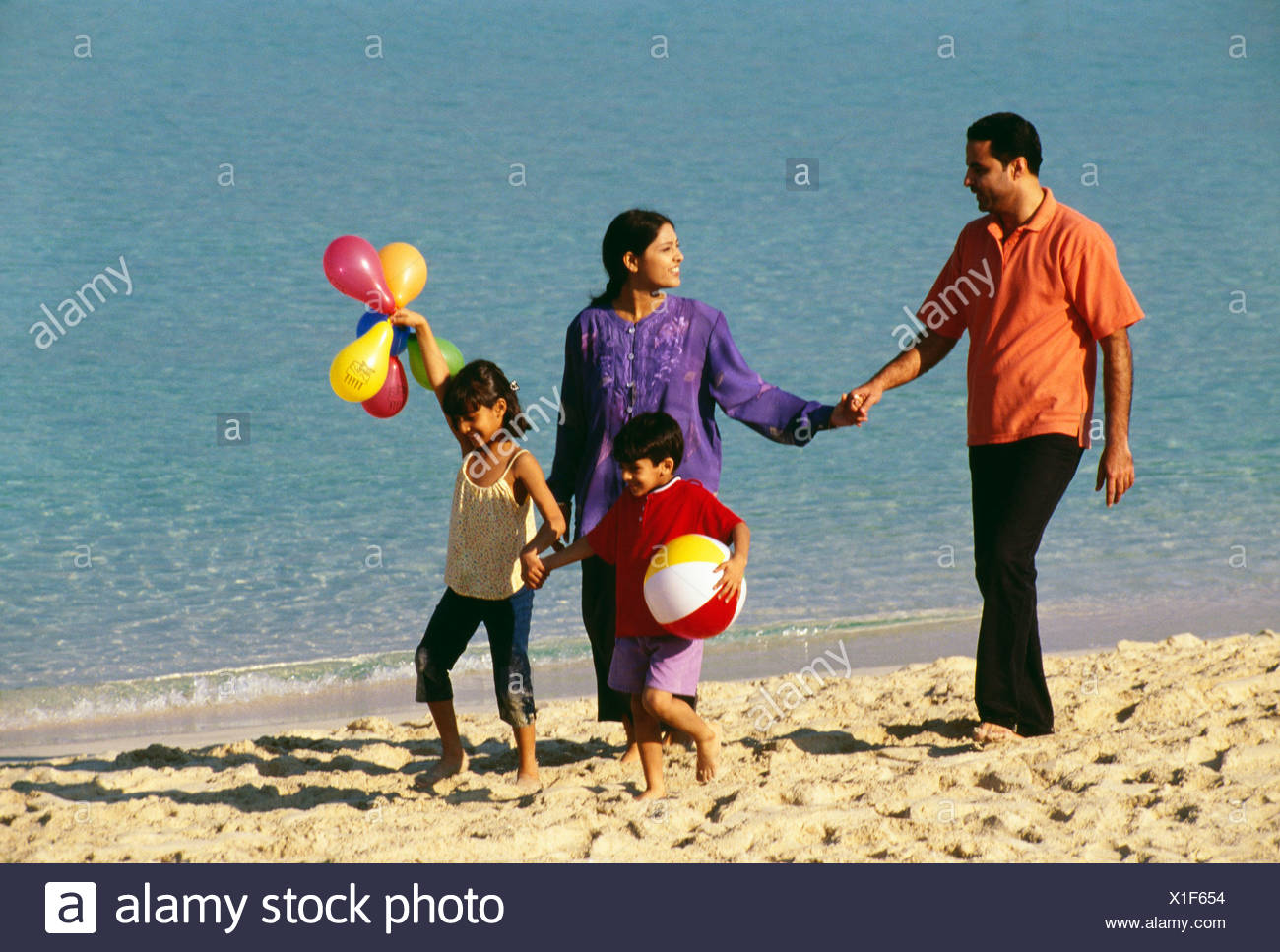 A family takes a stroll at the beach on a sunny day. Stock Photo
