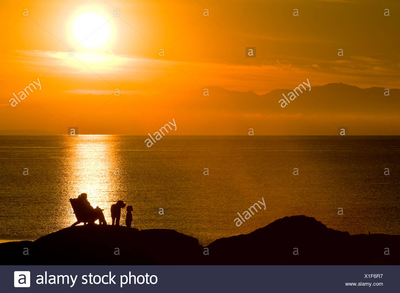 A mom and toddler are silhouetted by the sunset on an oceanside rock off Beach Drive, Victoria BC. - Stock Image