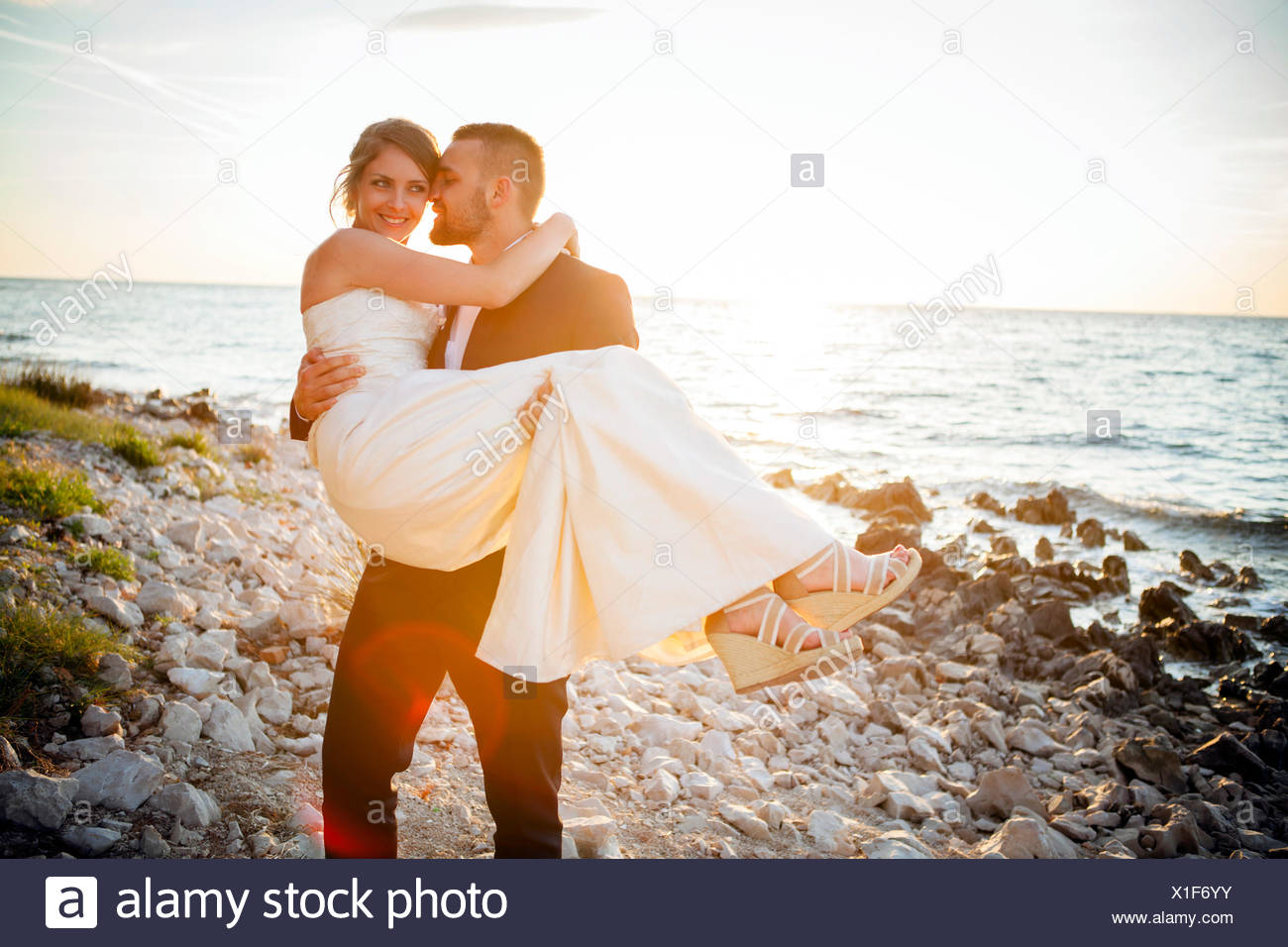 Groom carrying bride on pebble beach at sunset - Stock Image