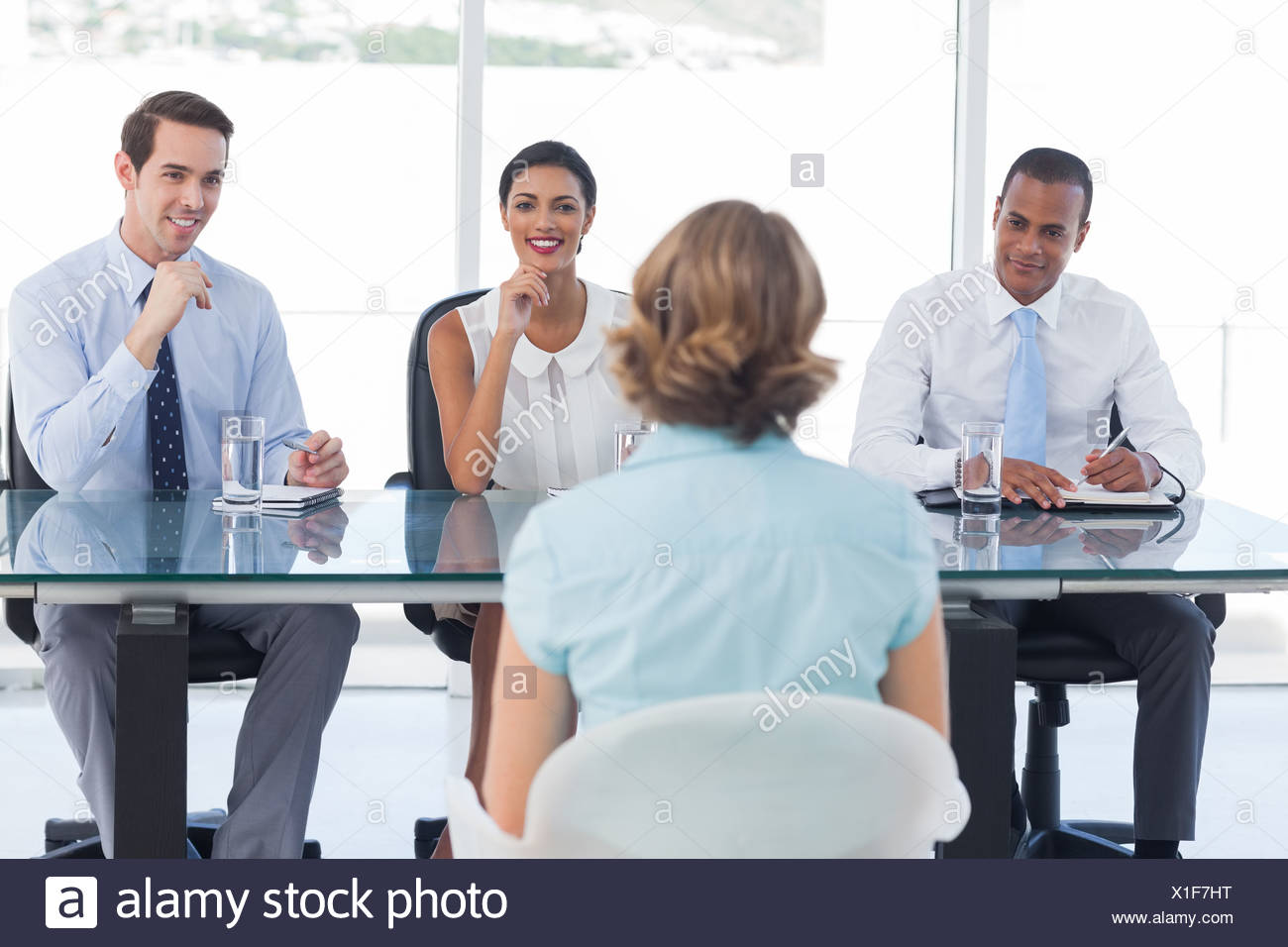 Recruitment consultants smiling in front of a job applicant - Stock Image