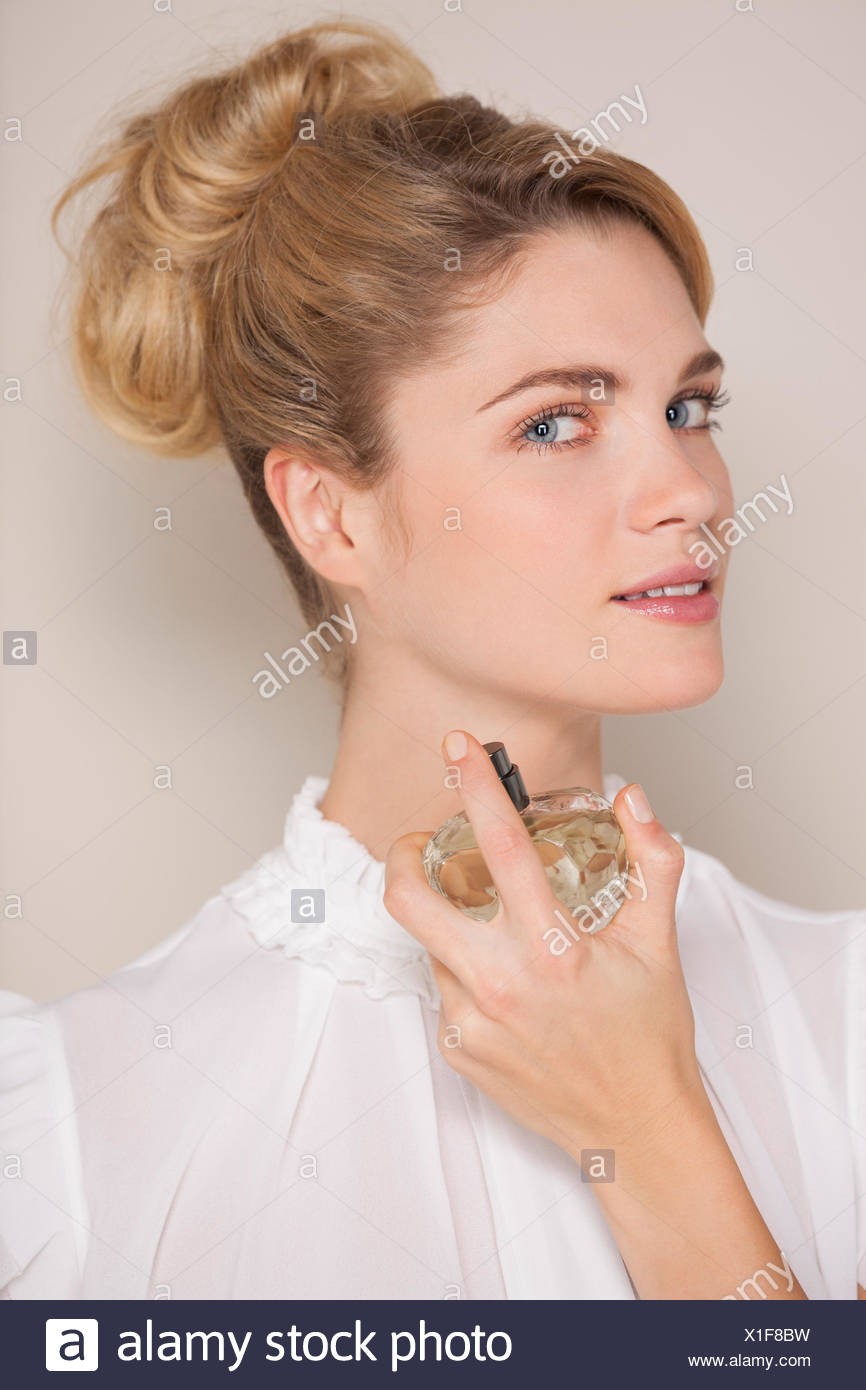 Beautiful woman applying perfume - Stock Image
