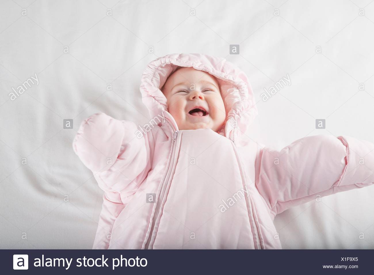 six months age cute baby dressed up in pink fluffy winter snowsuit snug hoodie clothes lying on white sheet bed smiling happy face. - Stock Image