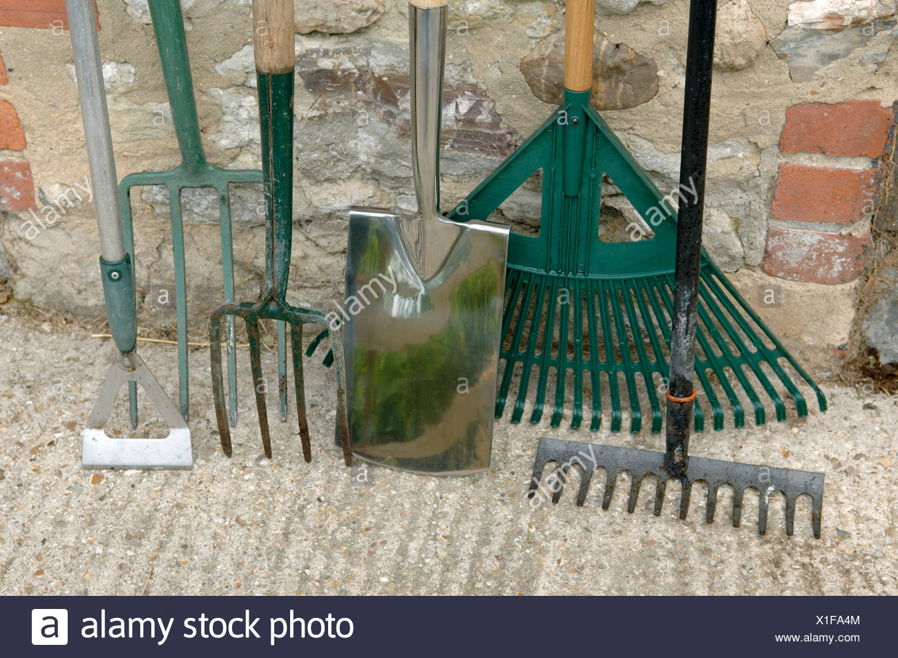 Garden tools spade hoe forks and rakes leaning against an outhouse wall - Stock Image