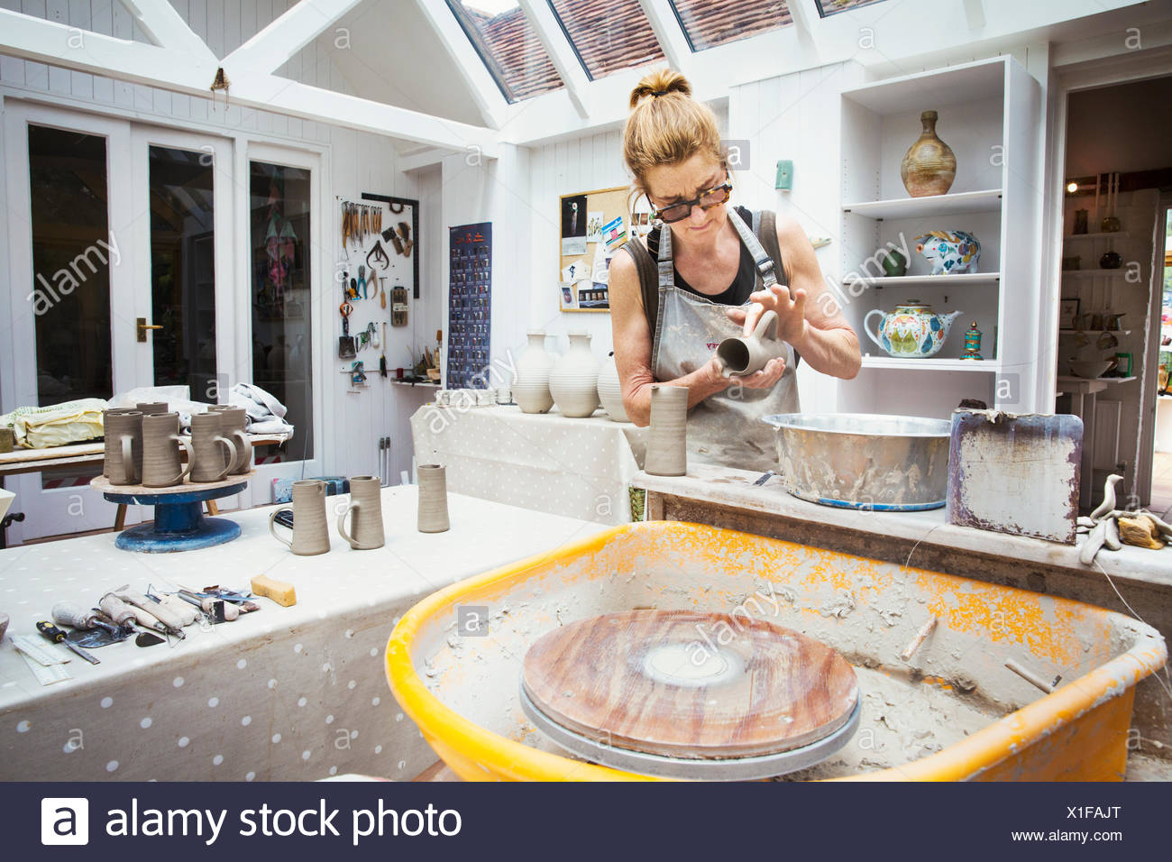 A potter handling a wet clay pot, preparing it for kiln firing. - Stock Image