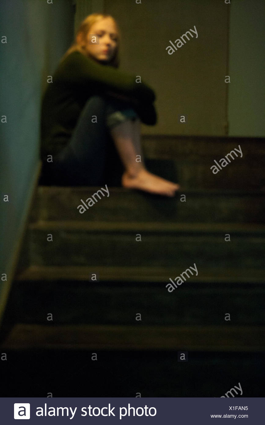 Woman sitting alone in stairwell - Stock Image