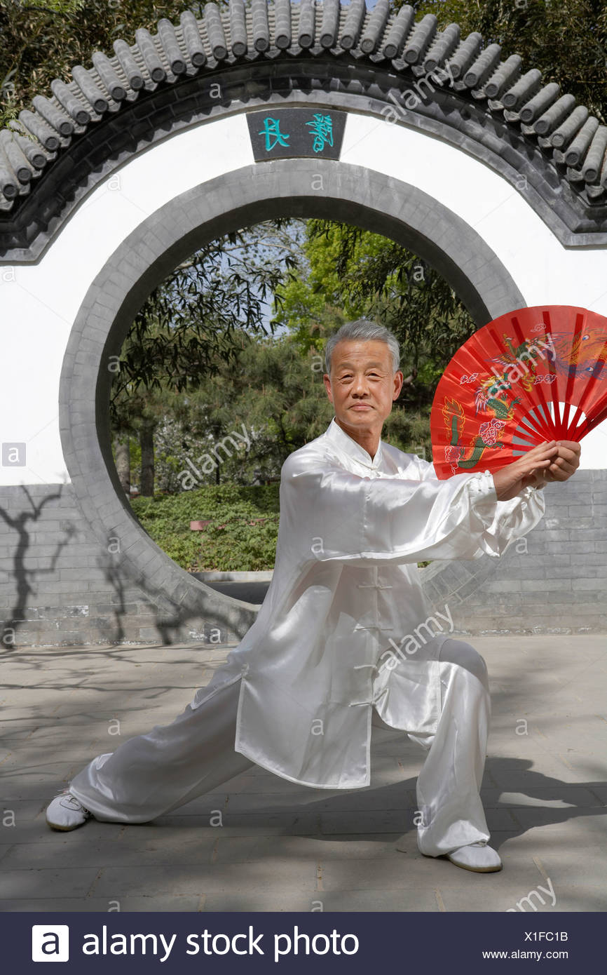 Elderly Man Practicing Martial Arts With A Fan - Stock Image