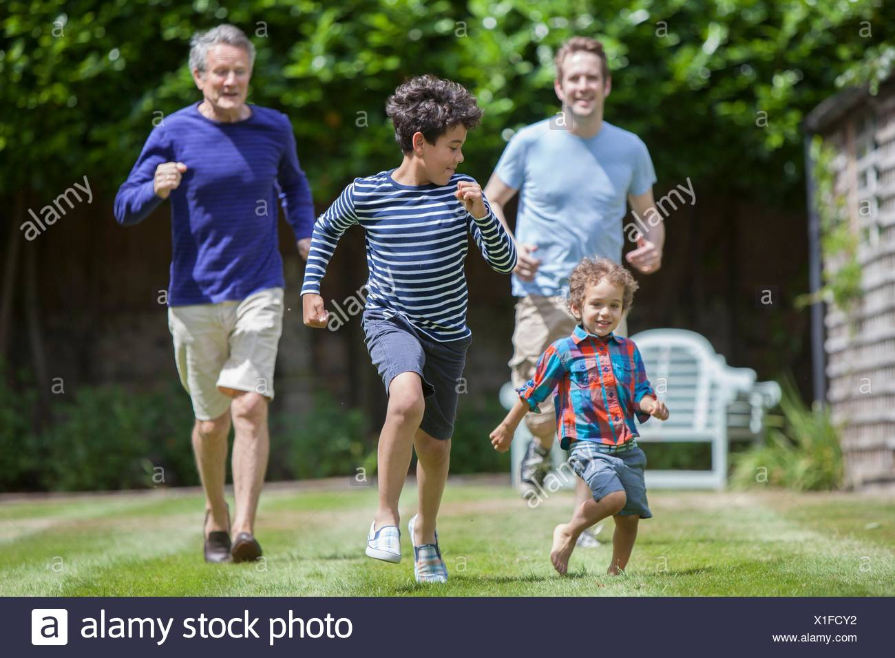 Three generation family fooling around in garden - Stock Image