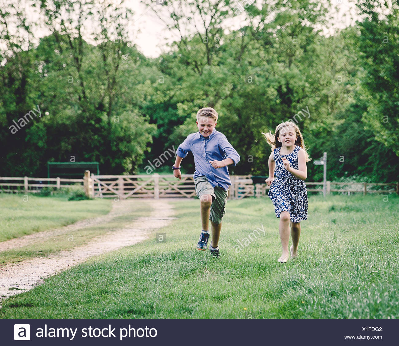 Two children racing each other in a field - Stock Image