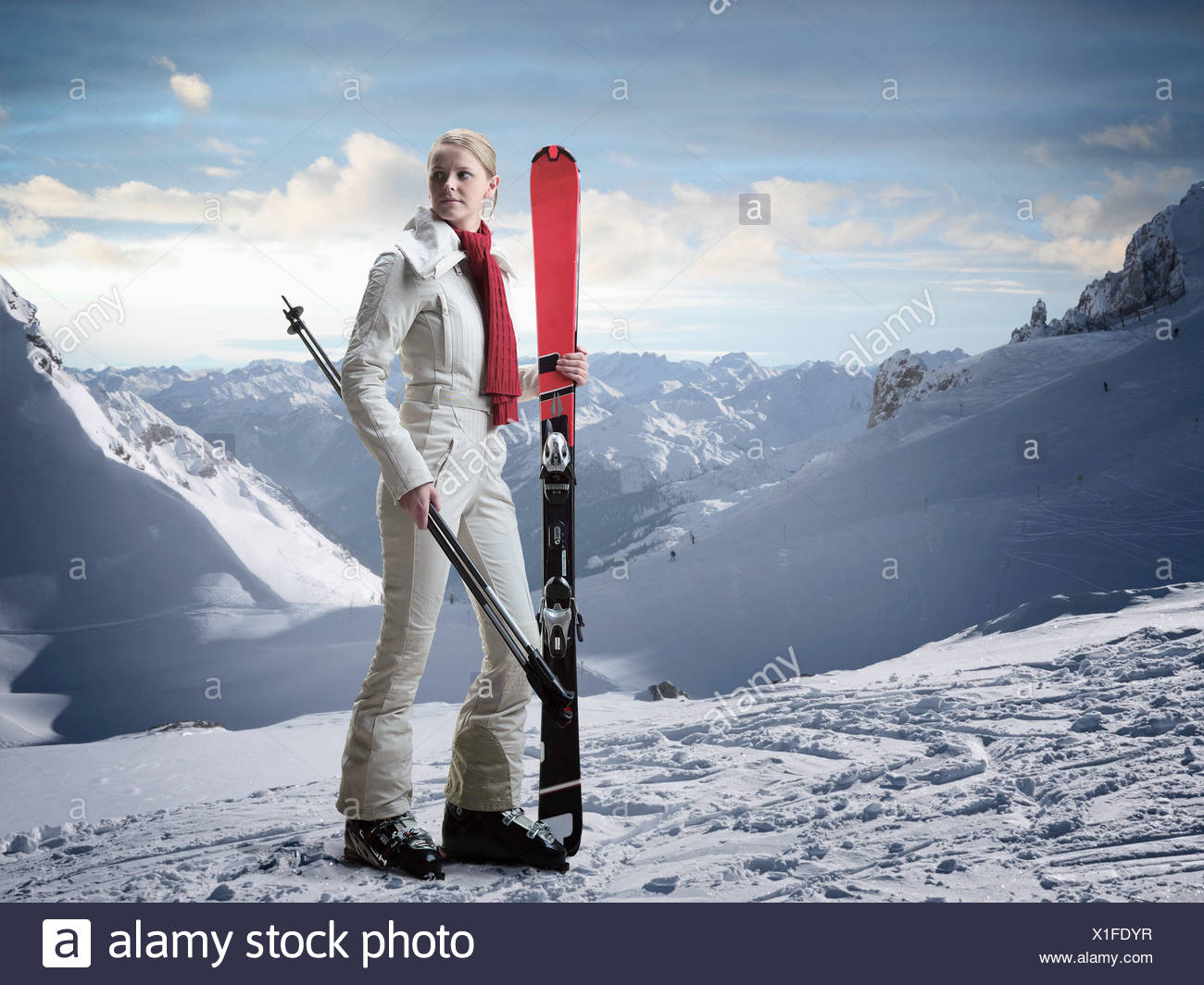 Woman carrying skis on snowy slope - Stock Image