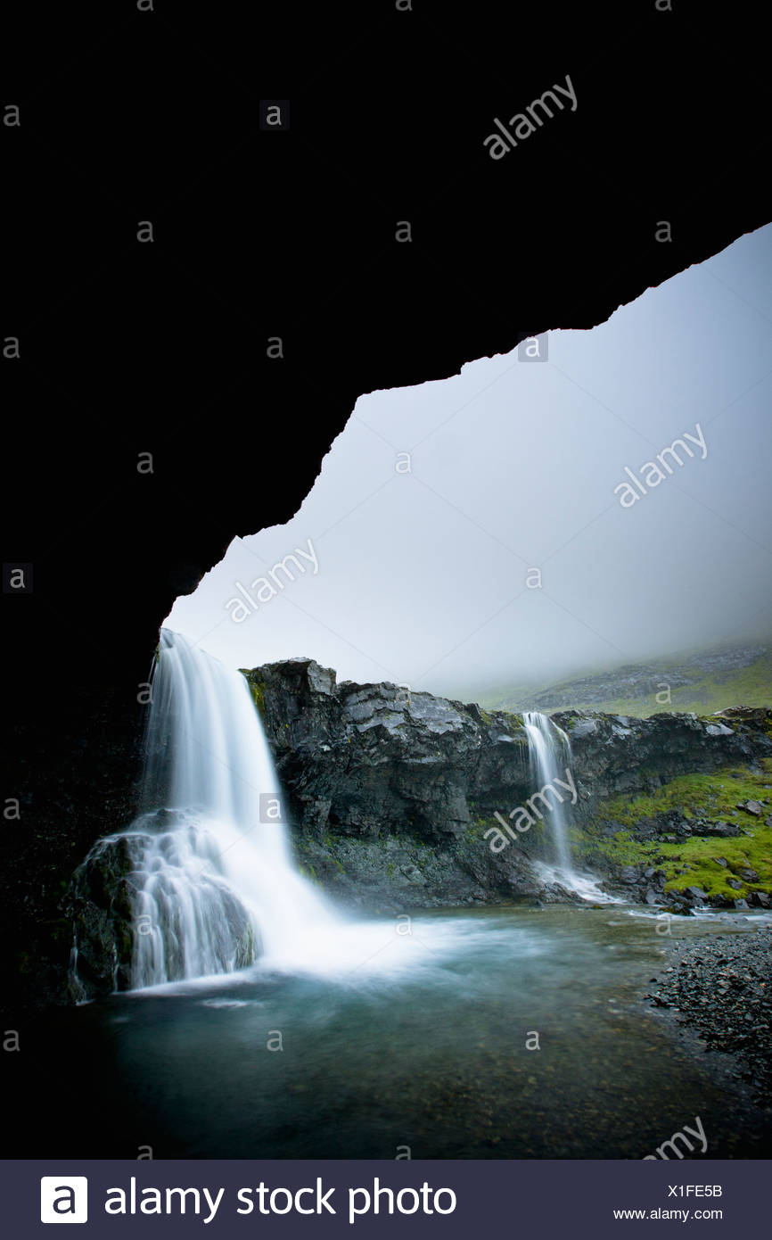 Waterfalls Over A Rock Ledge As Viewed From Inside A Cave; Iceland - Stock Image