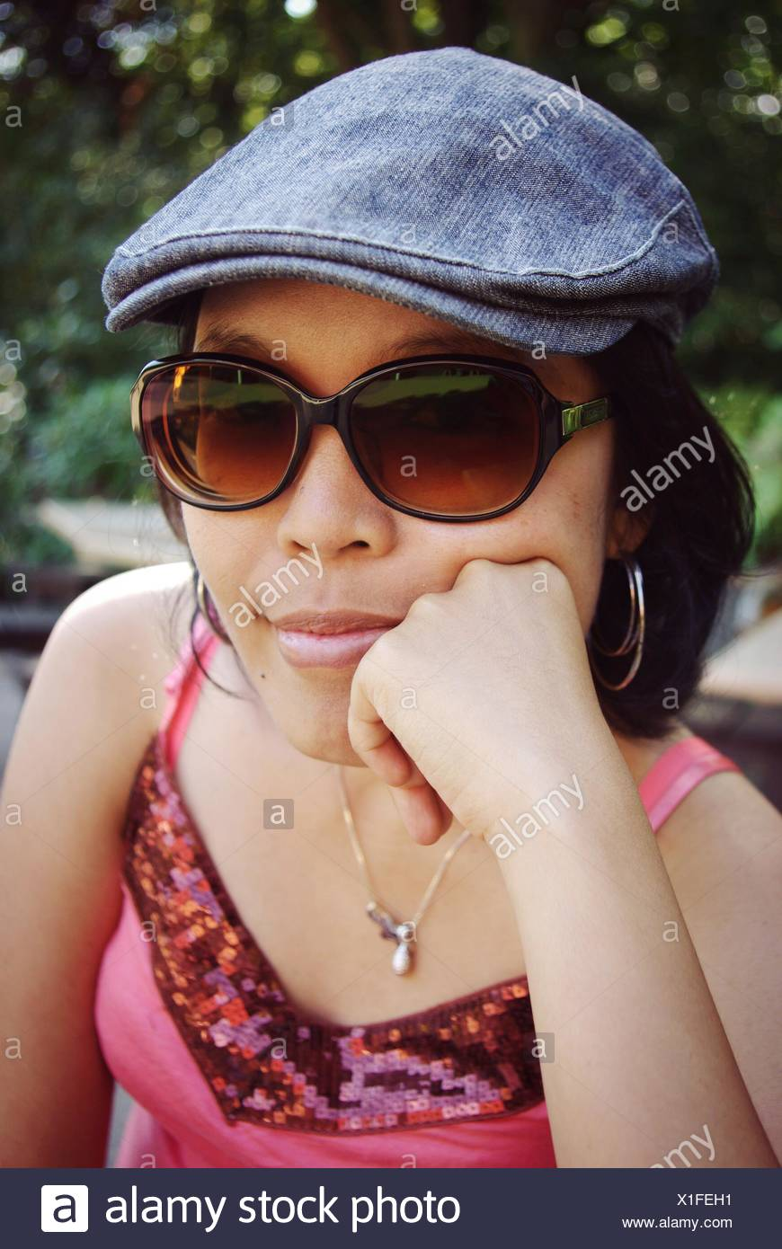caa75c19820cc Close-Up Portrait Of Young Woman Wearing Sunglasses Sitting In Park ...