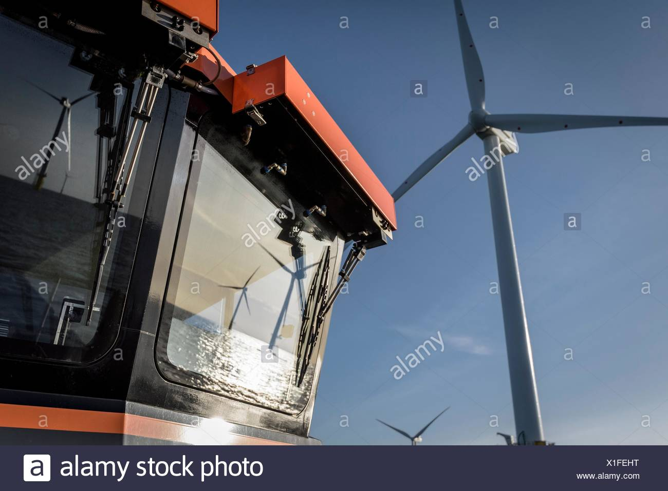 Reflections of offshore wind farm on boat at sea - Stock Image