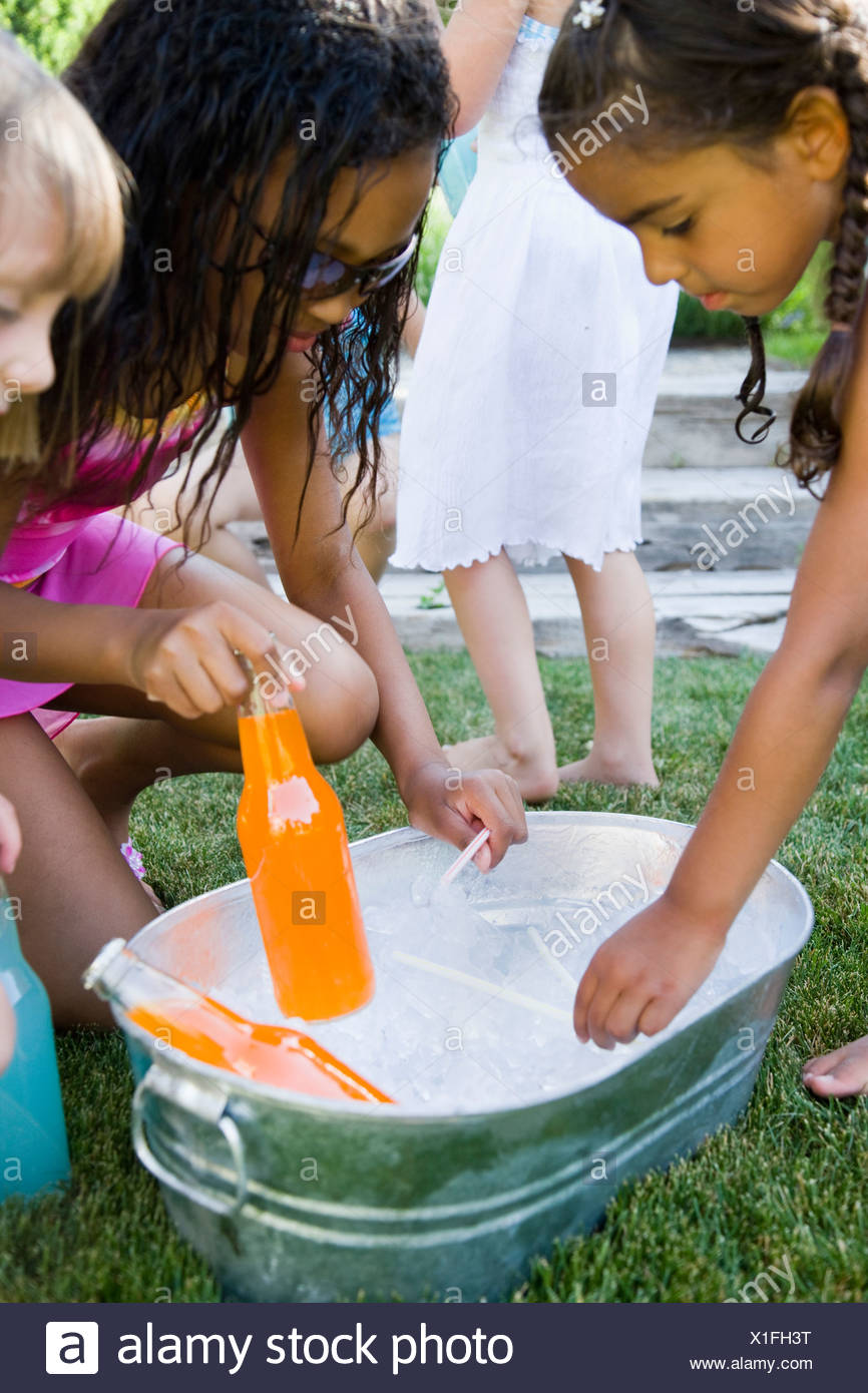 children picking sodas out of a bin of ice - Stock Image