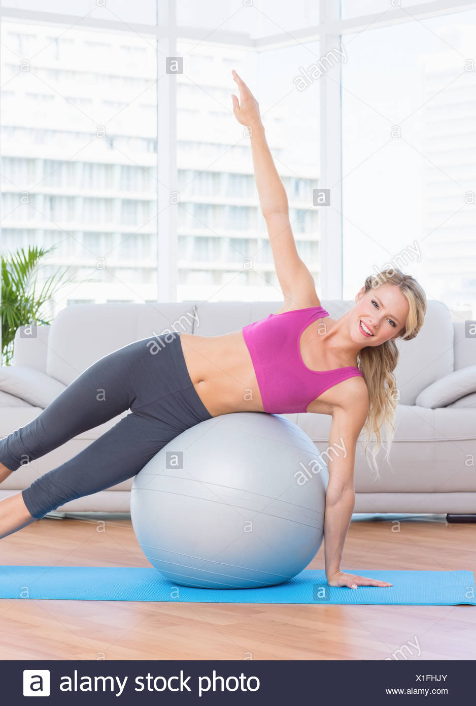 Happy fit blonde doing side plank with exercise ball - Stock Image