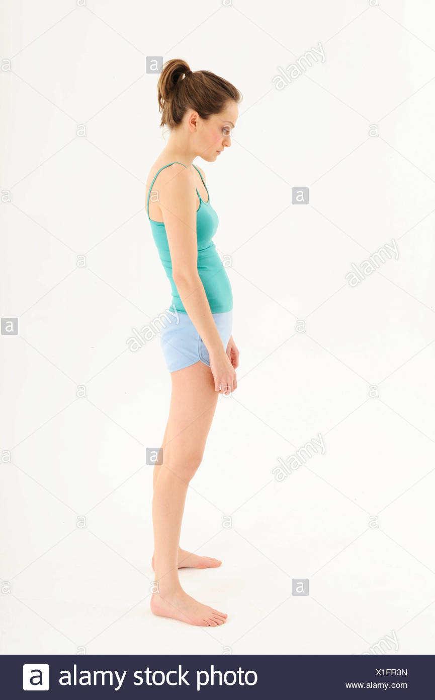 Female brunette hair tied into ponytail, wearing a green camisole and blue shorts, standing in bad posture, hunched shoulders, - Stock Image