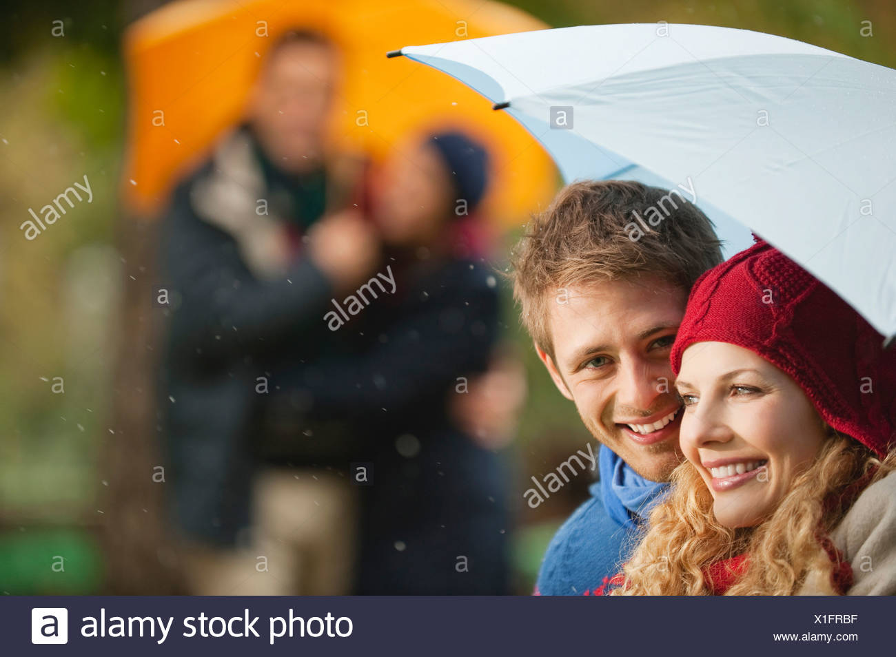 Germany, Bavaria, English Garden, Four persons in beer garden, holding umbrella, smiling, portrait, close-up - Stock Image