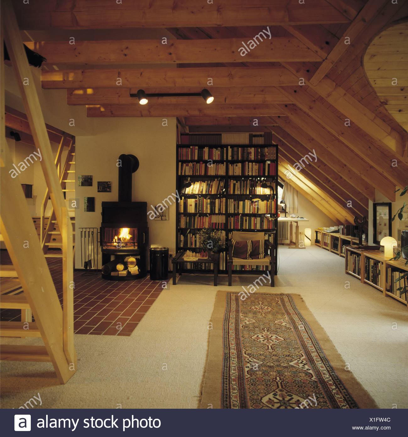 Bookshelves Beside Black Stove In Large Openplan Attic