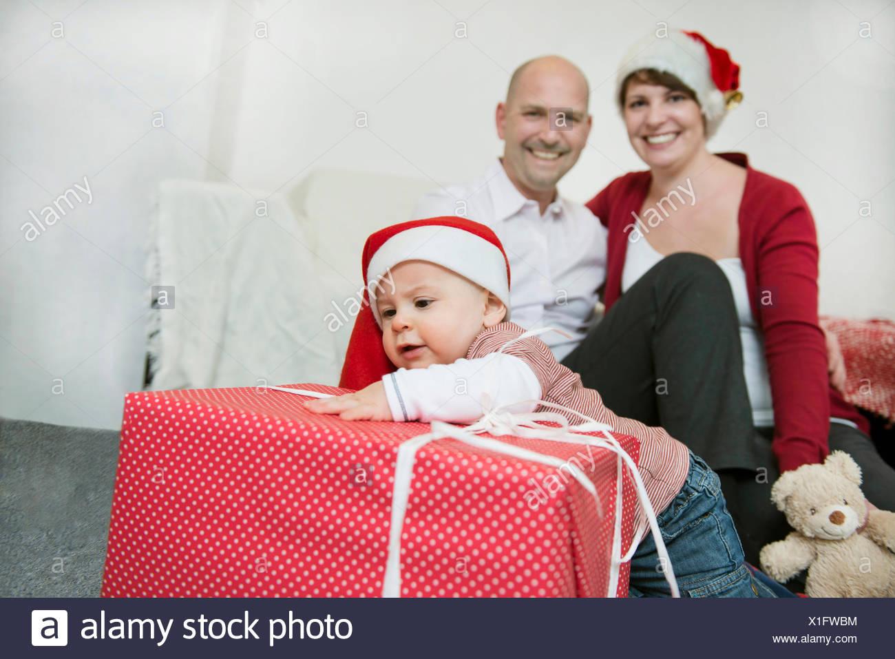 Family celebrating Christmas with Christmas caps and Christmas present - Stock Image