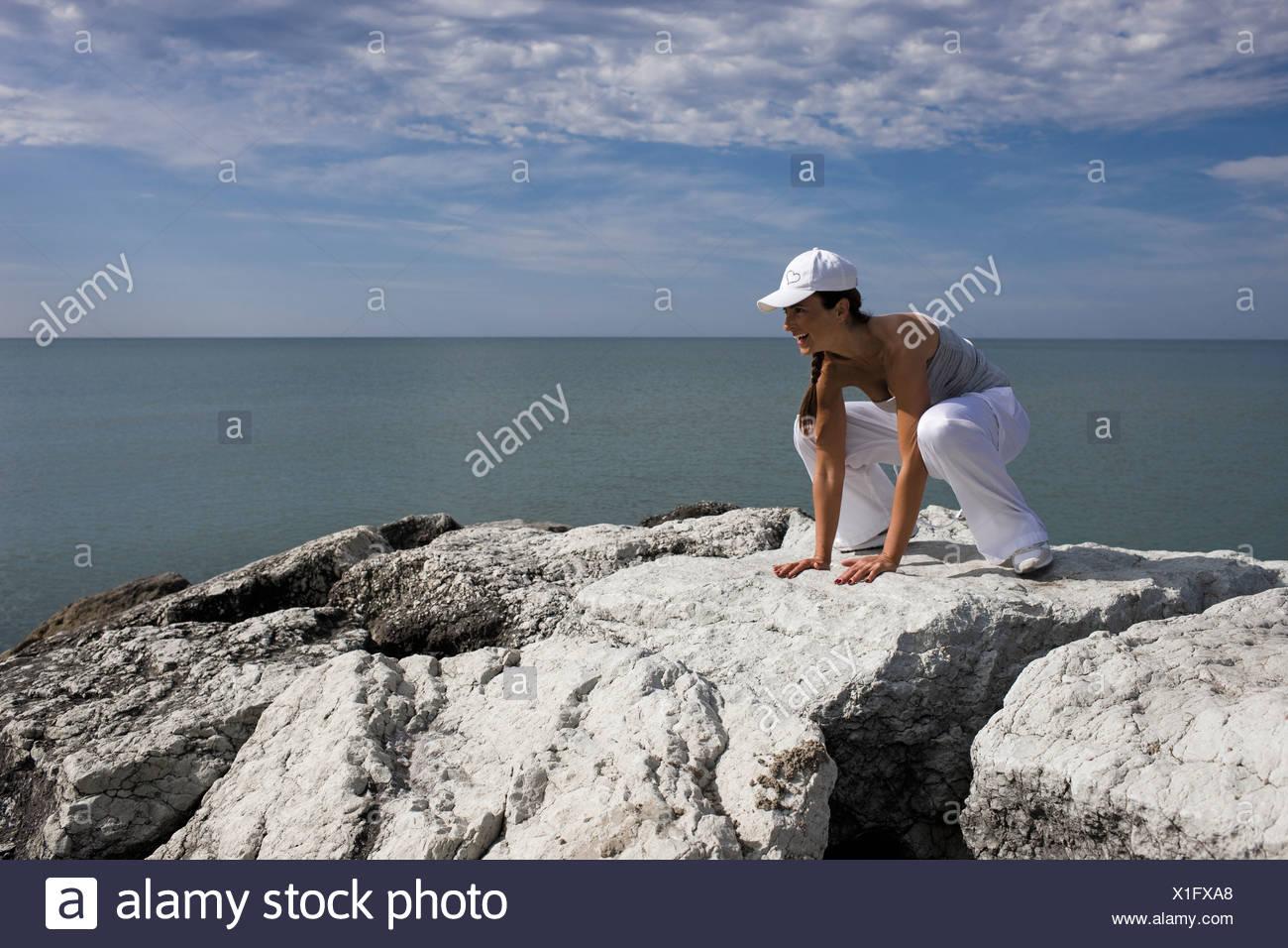 Woman hunkering down on rocks - Stock Image