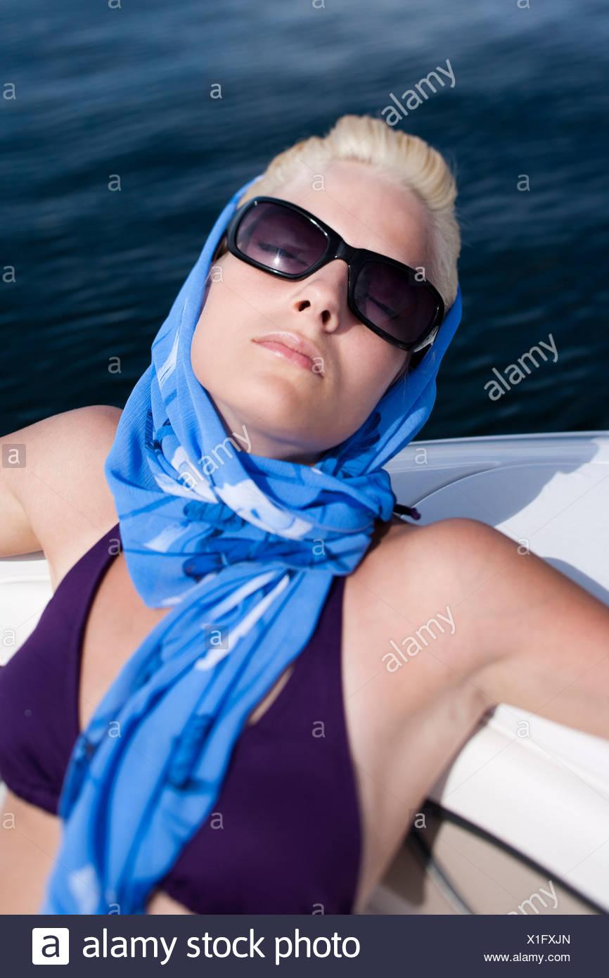 47e0397094 Woman in bikini on boat with headscarf and sunglasses - Stock Image