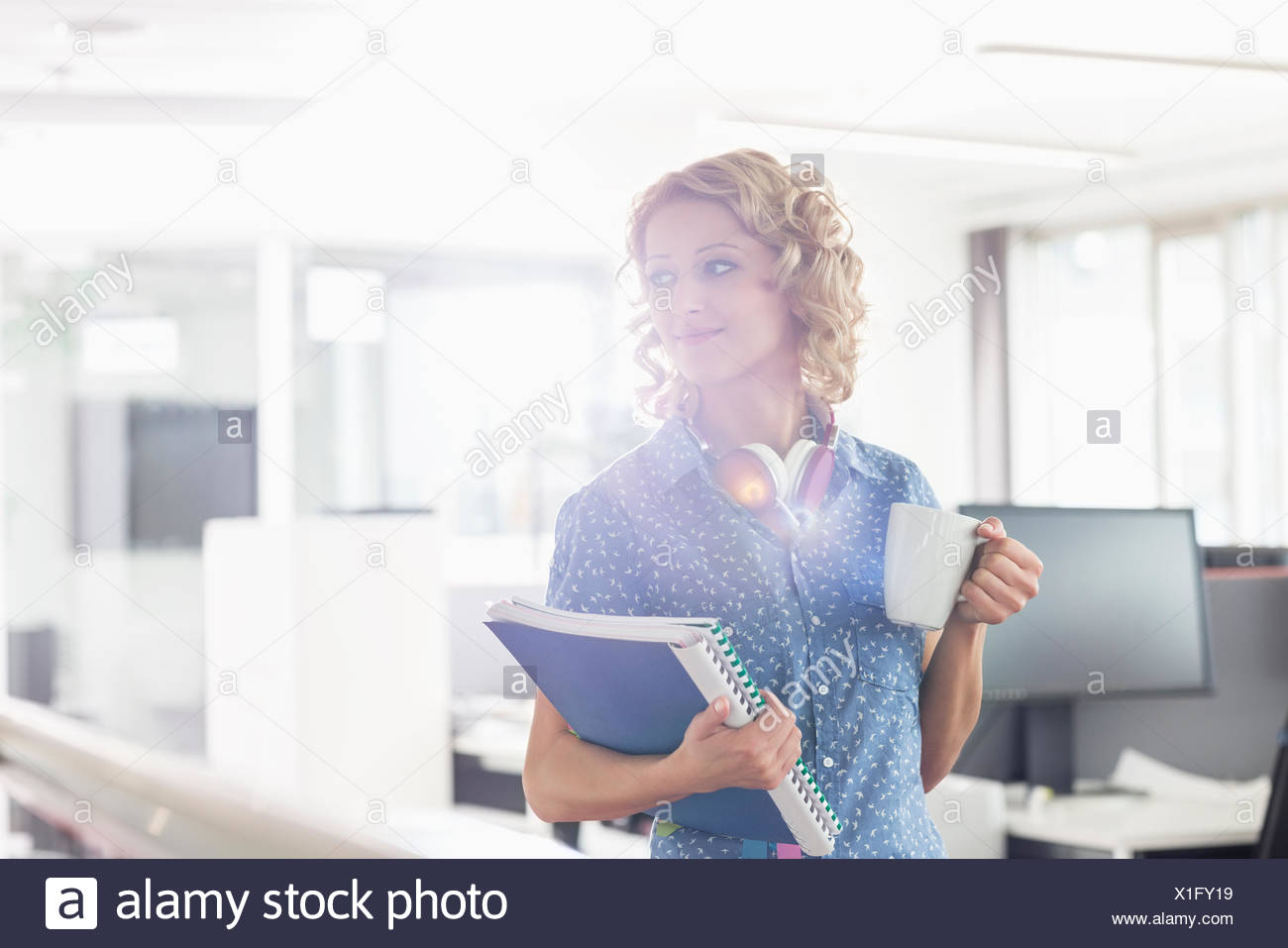 Businesswoman having coffee while holding files in creative office - Stock Image