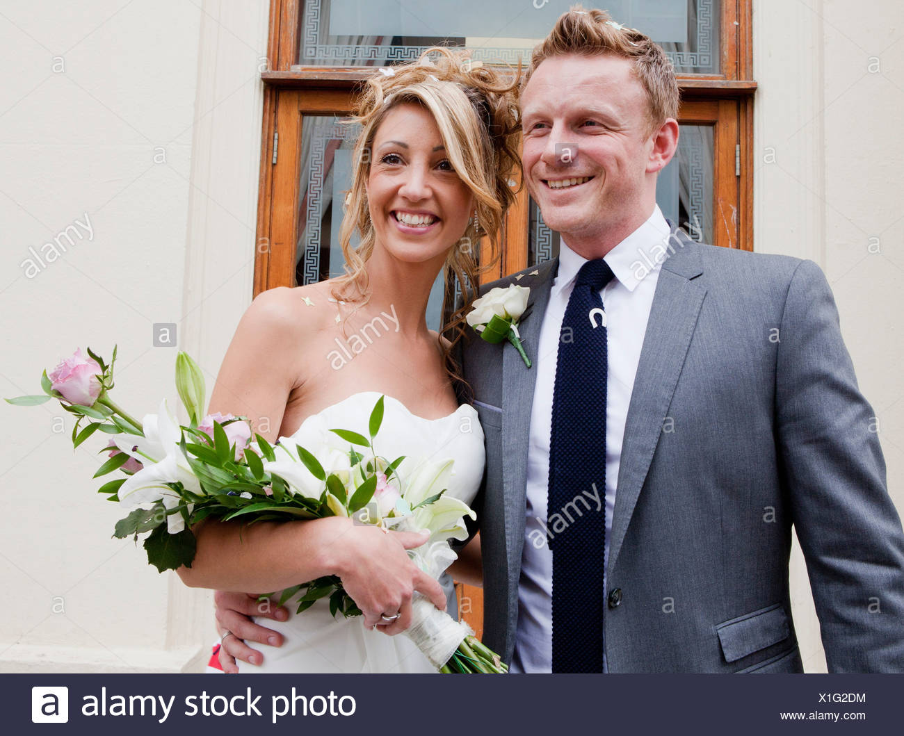 Bride and groom smiling at wedding ceremony - Stock Image
