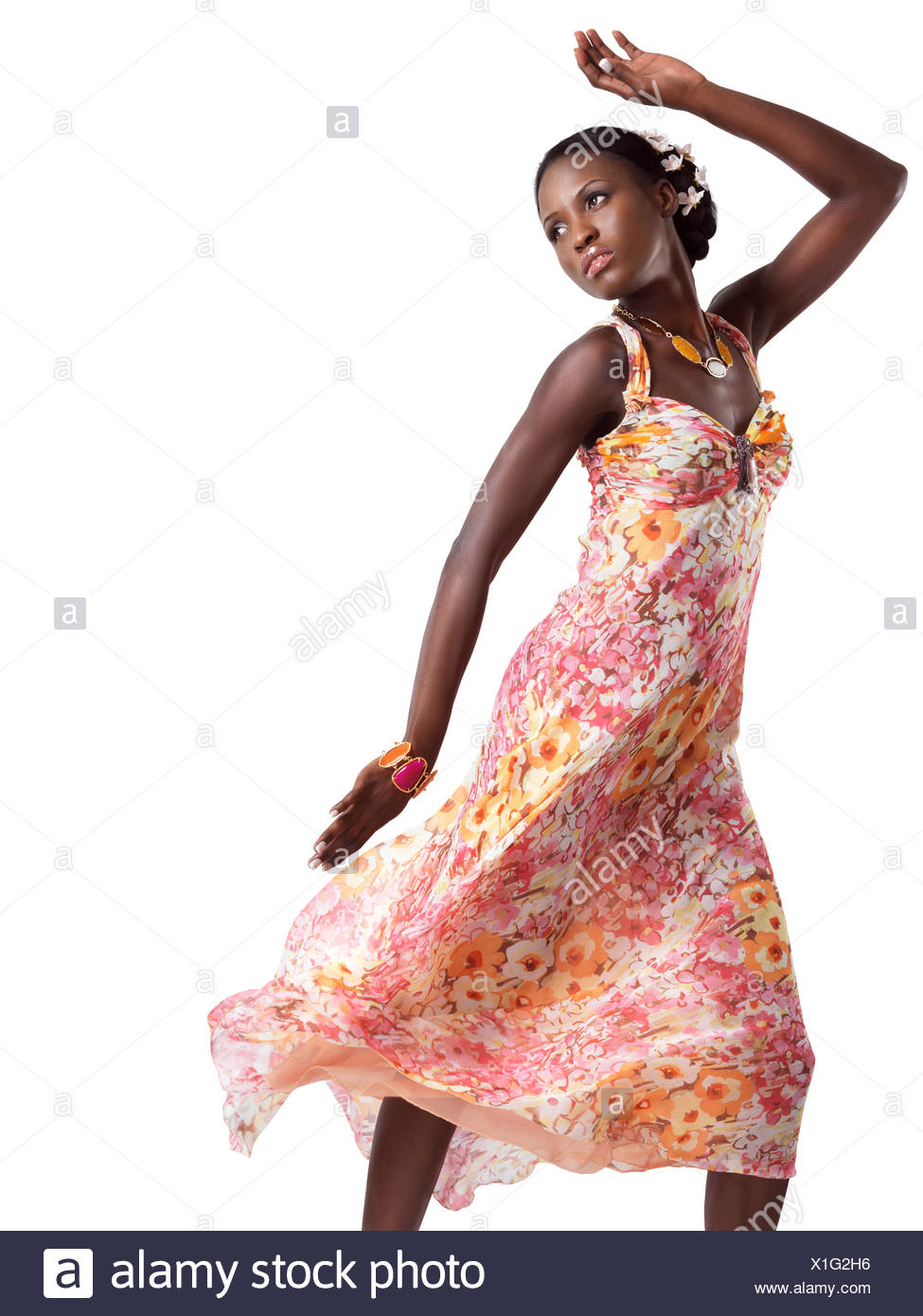 445ff3c6bd9df Beautiful young black woman dancing in a pink floral summer dress isolated  on white background