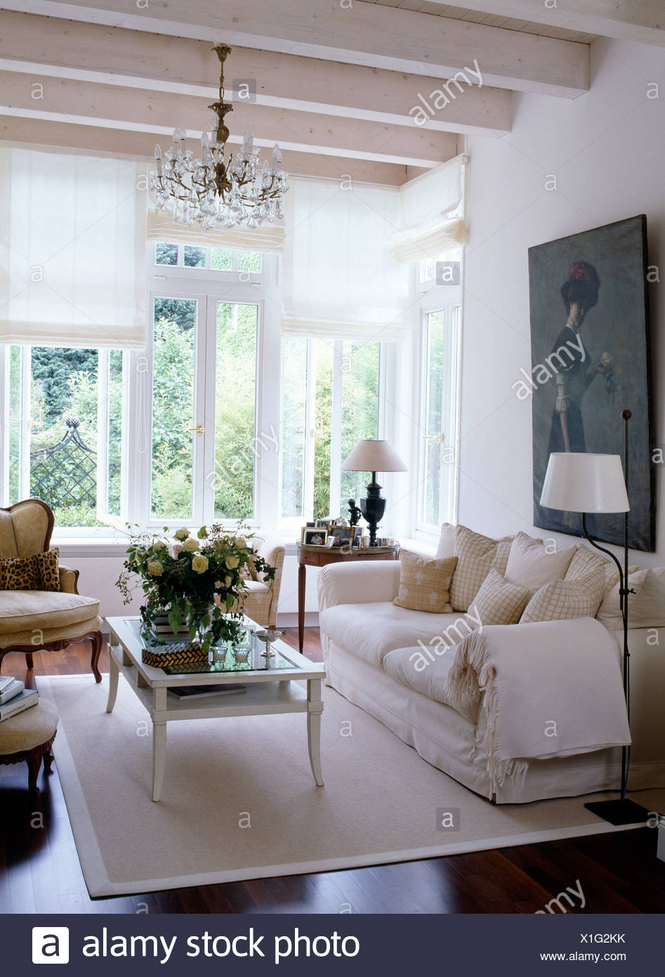 Coffee table on white rug in front of white sofa in country ...