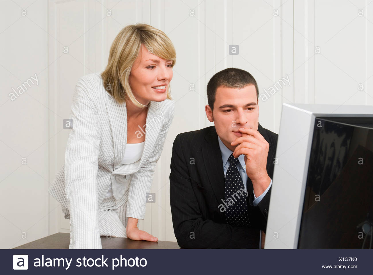 Business people looking at computer in office - Stock Image