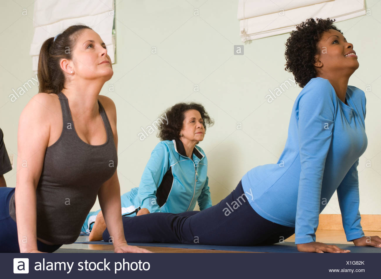 Women Stretching Backs in Yoga Class - Stock Image