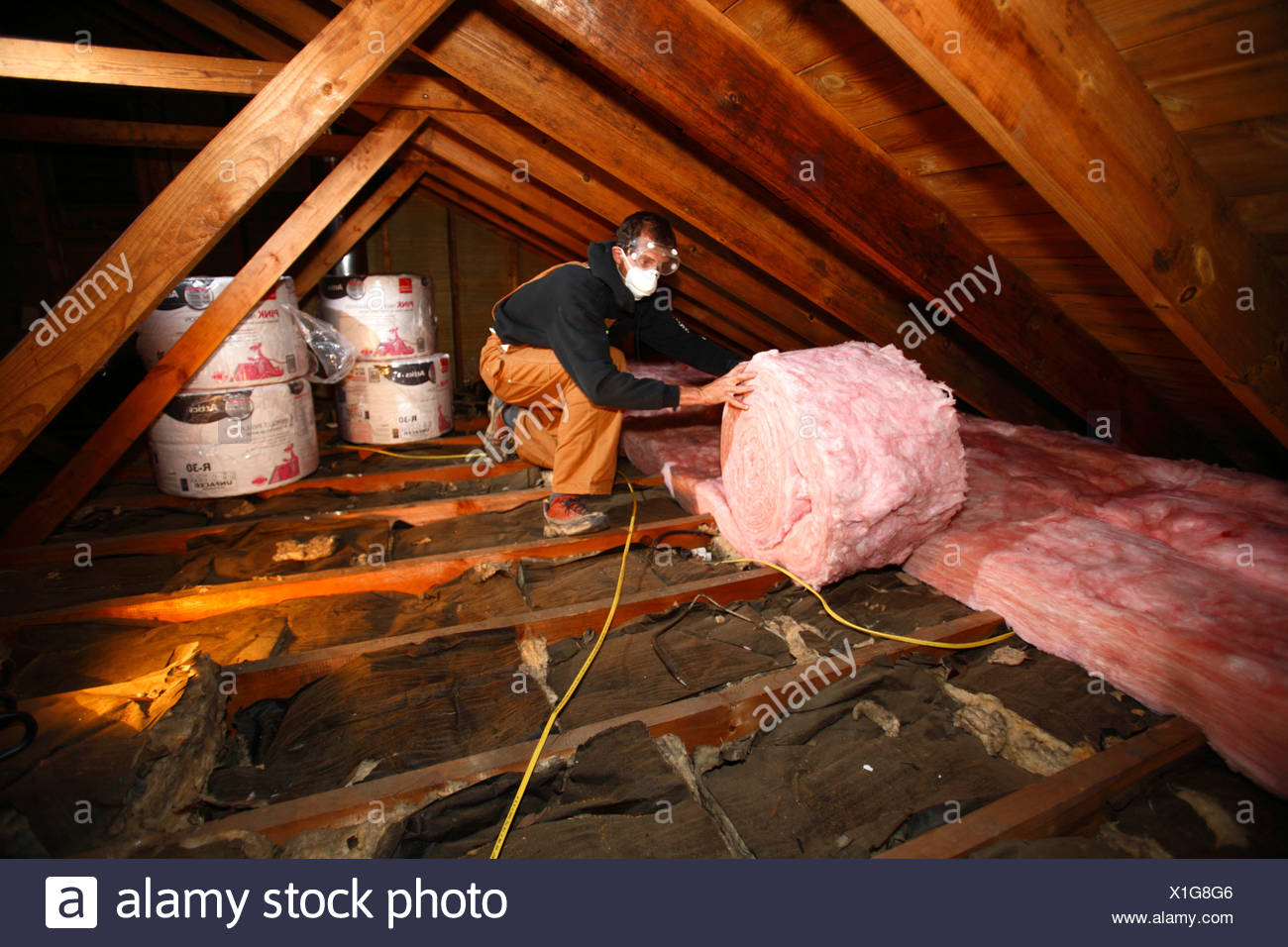 Man adds insulation to an attic - Stock Image