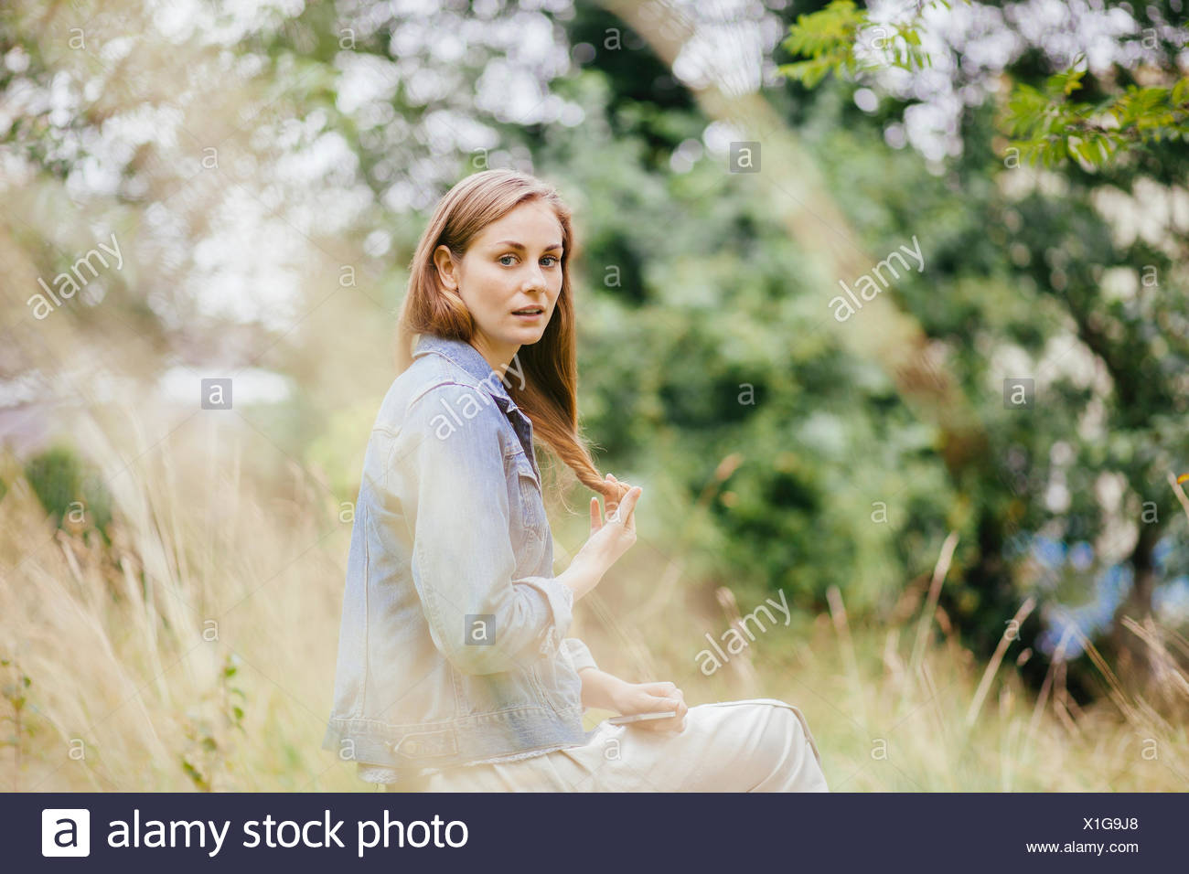 Portrait of young woman with hand in hair in field - Stock Image