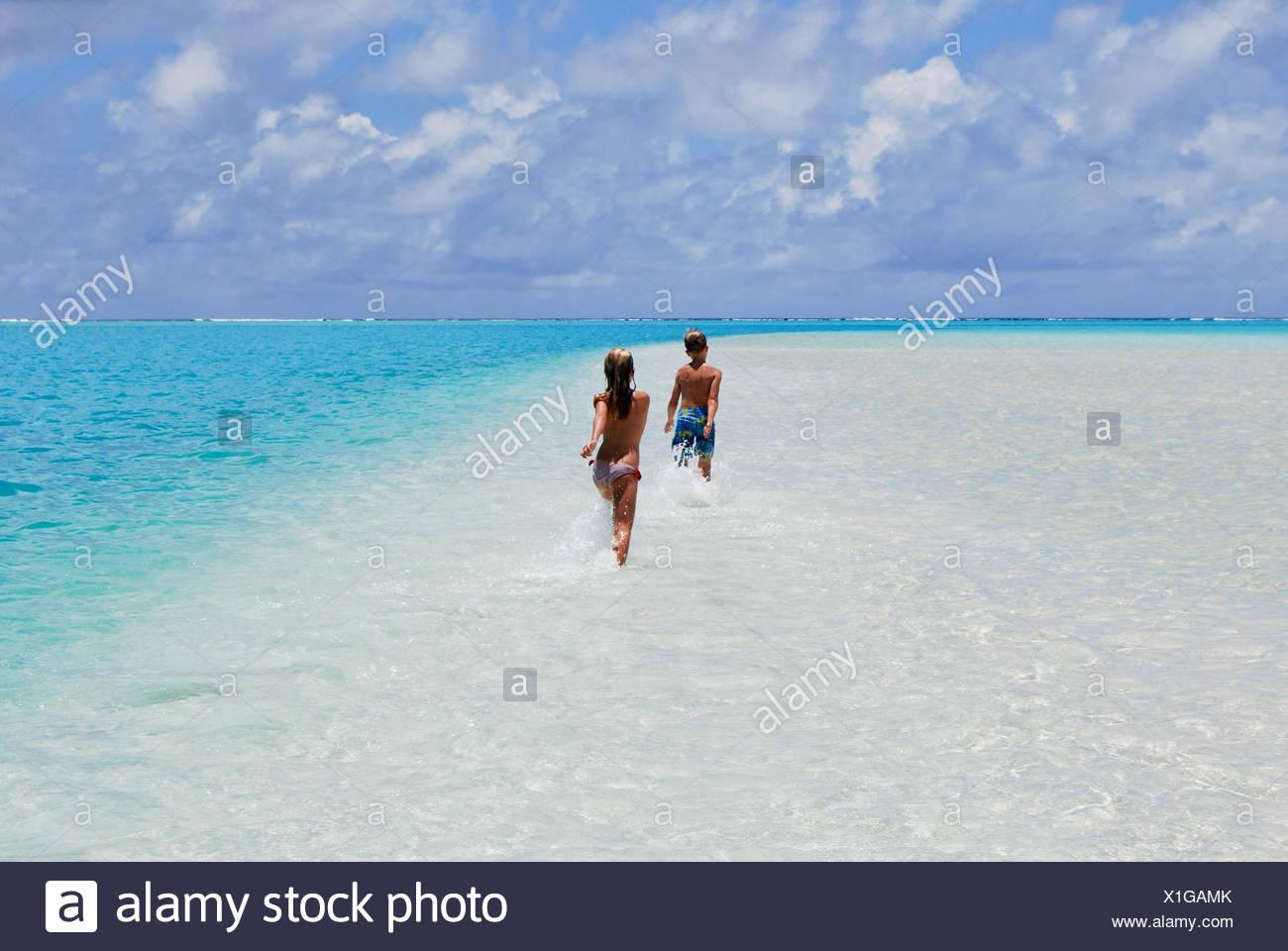 Two children running on sandbar in ocean, Aitutaki, Cook Islands - Stock Image