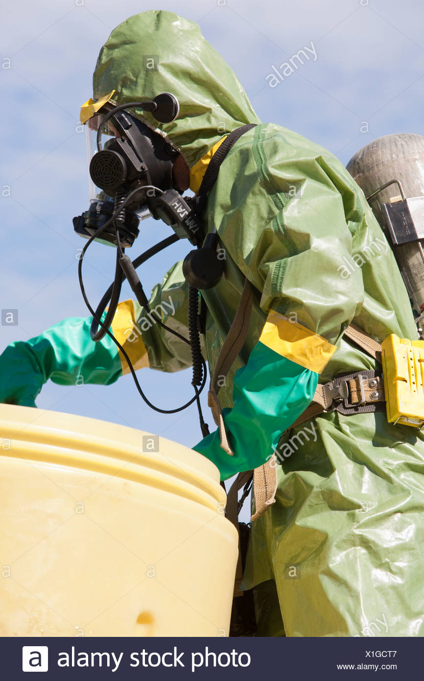 HazMat firefighter pushing a salvage drum - Stock Image