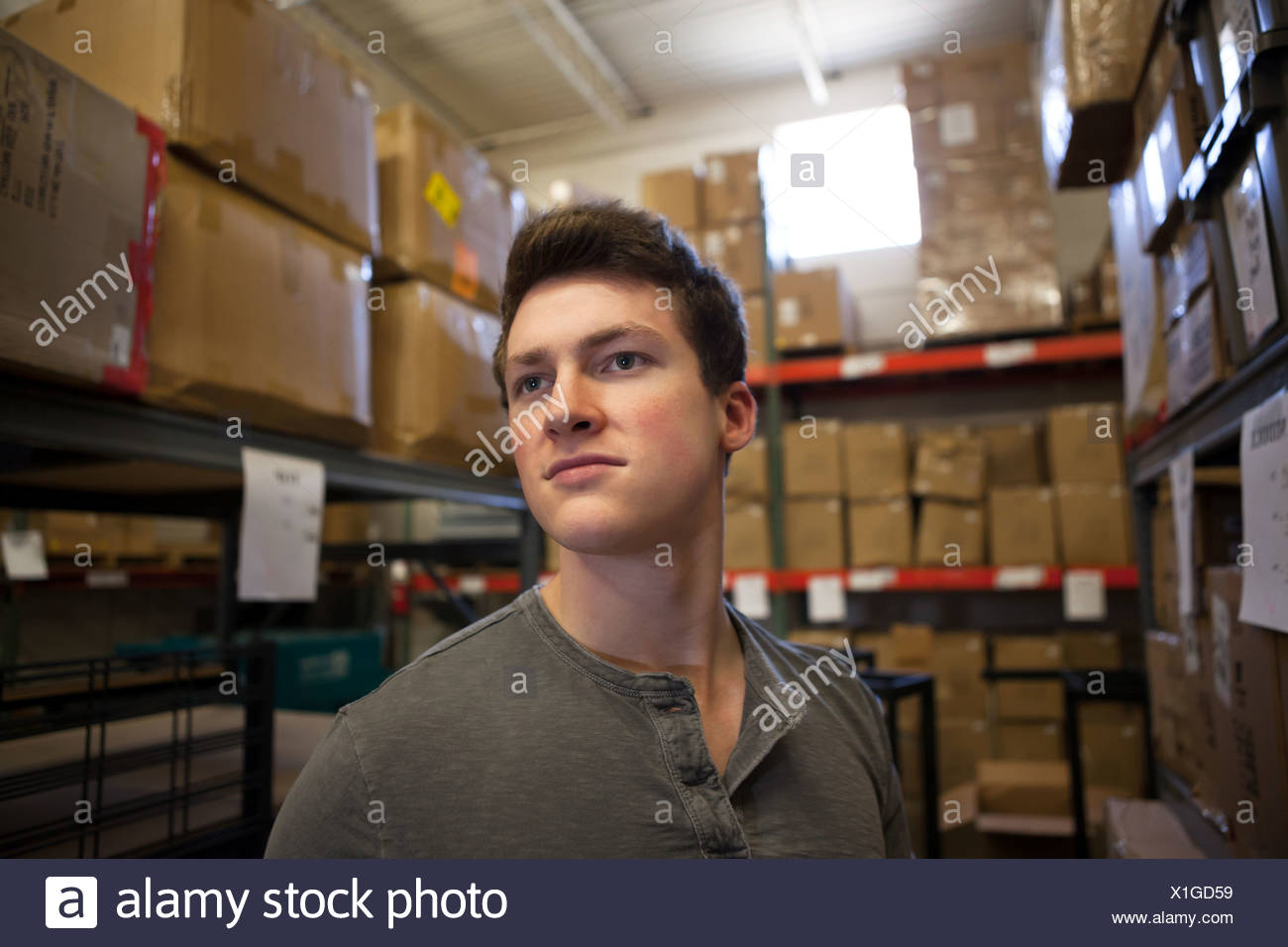 Worker standing in warehouse - Stock Image