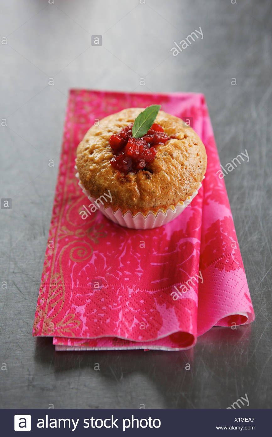 Close up of muffin with strawberry pieplant relish on napkin - Stock Image