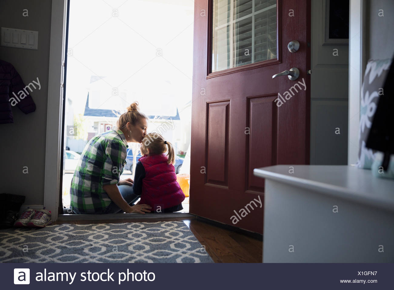 Mother kissing daughter forehead in doorway - Stock Image