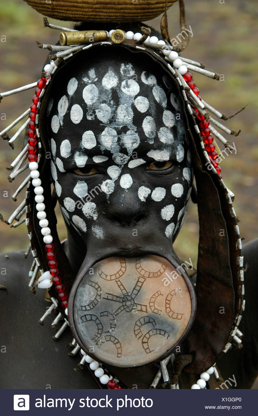 Portrait of a young woman from the Mursi tribe with a lip plate and white dots on her black face, near Jinka, Ethiopia, Africa - Stock Image