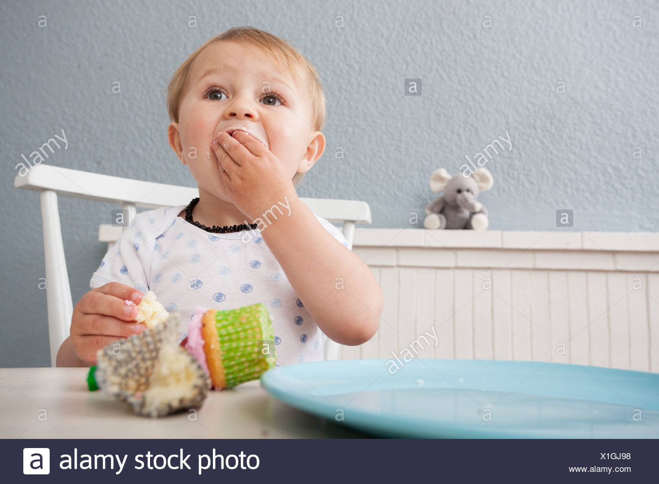 Baby boy eating cupcake - Stock Image