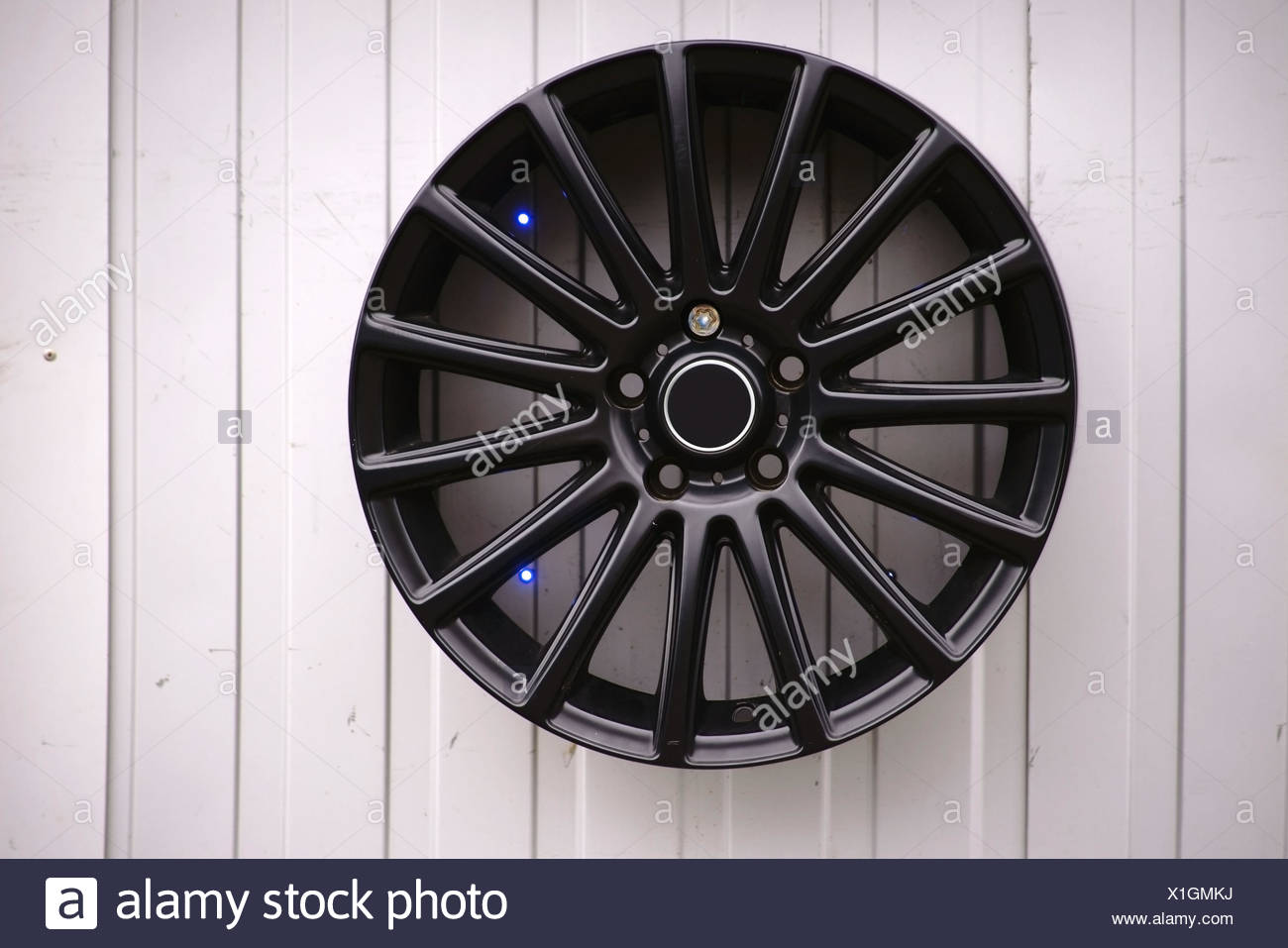 A black varnished wheel rim with LED lamps hanging on a tin facade for decoration. - Stock Image