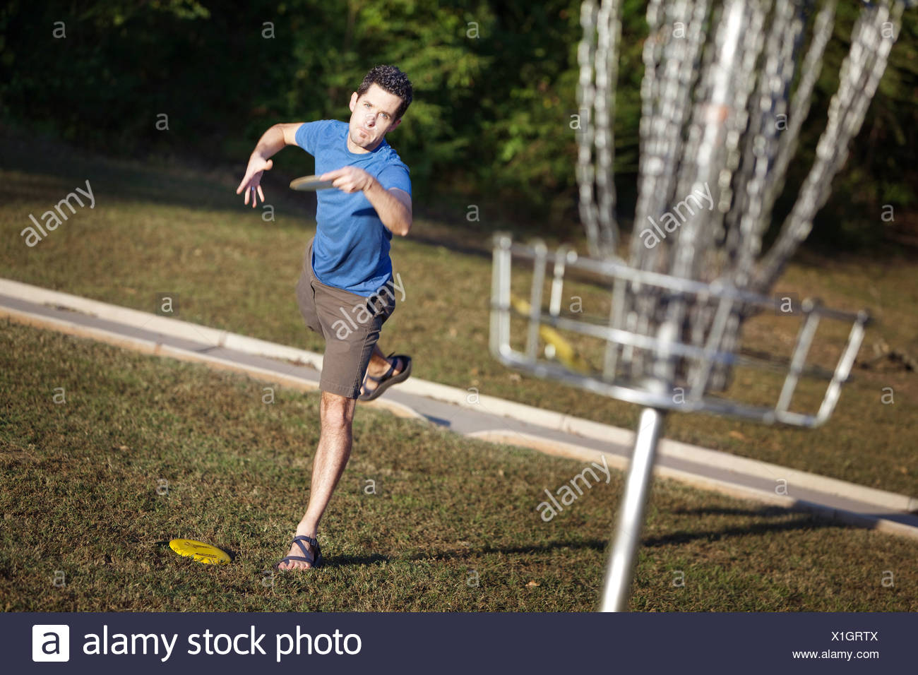 A man playing disc golf attempts a short putt. - Stock Image