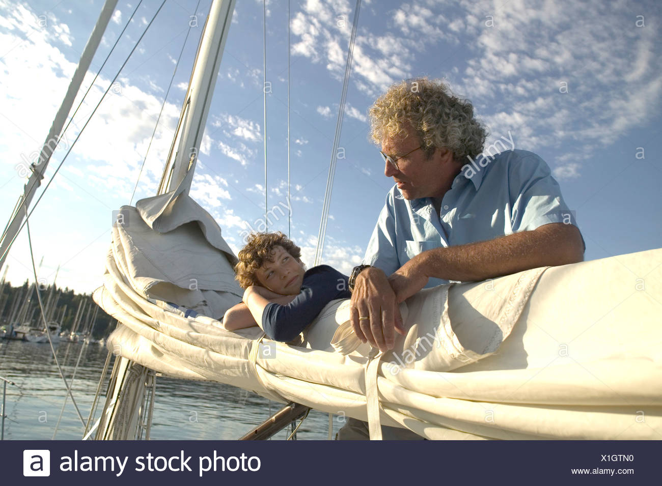 Father and son untying sail - Stock Image