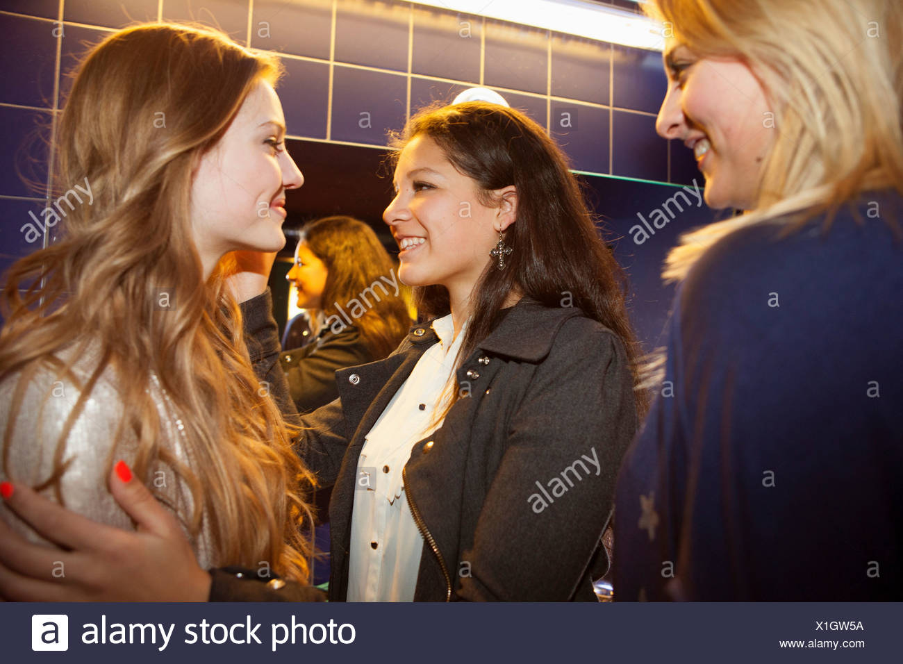 Three teenage girls chatting and smiling in toilets - Stock Image