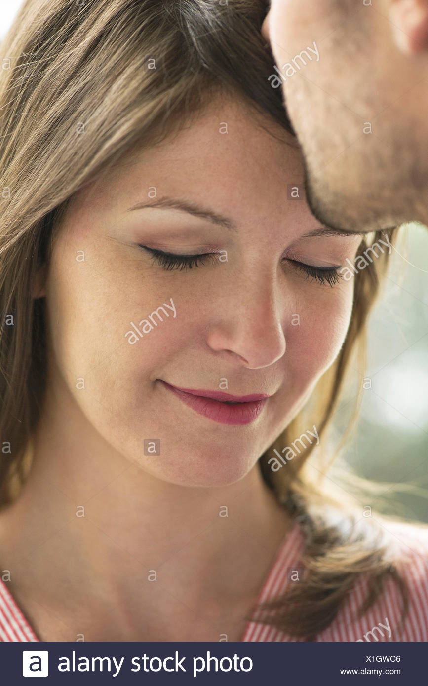 Man kissing woman's forehead, cropped - Stock Image